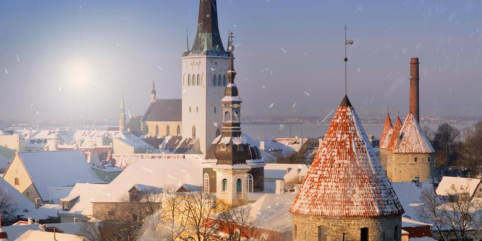 Solen står op bag et vinterklædt Tallinn.