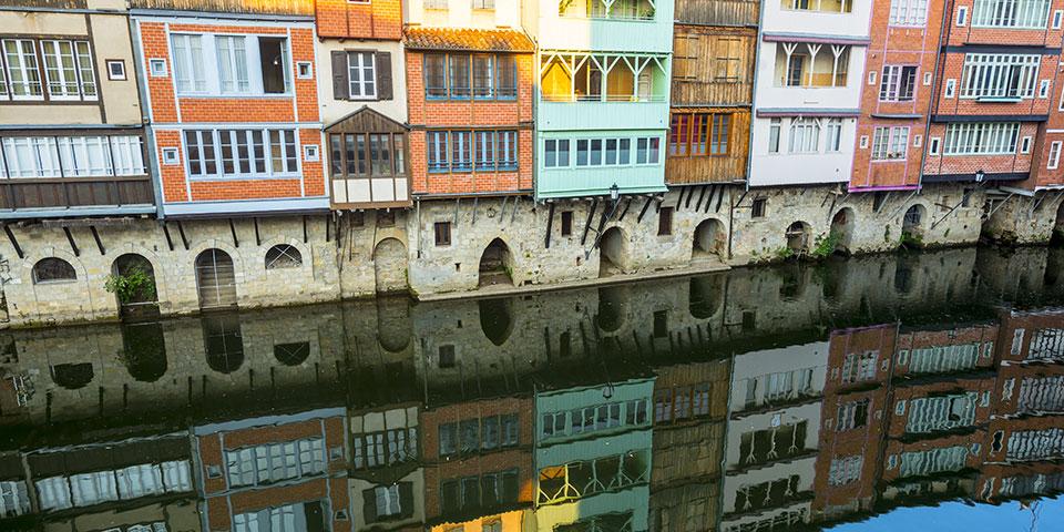 Huse spejler sig i vandet i Castres.