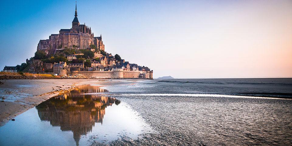 Solen går ned bag Mont Saint Michel.