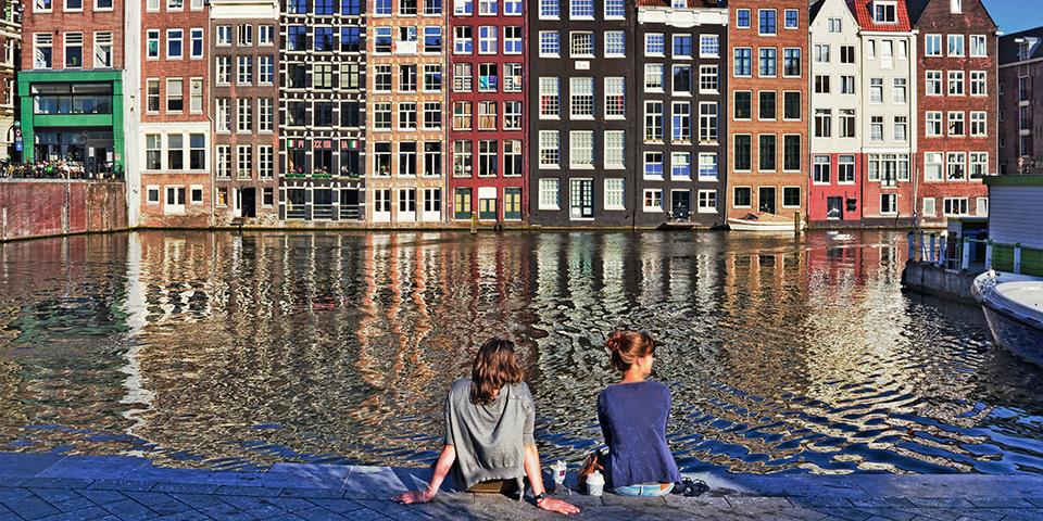 Piger ved kanal i Amsterdam.