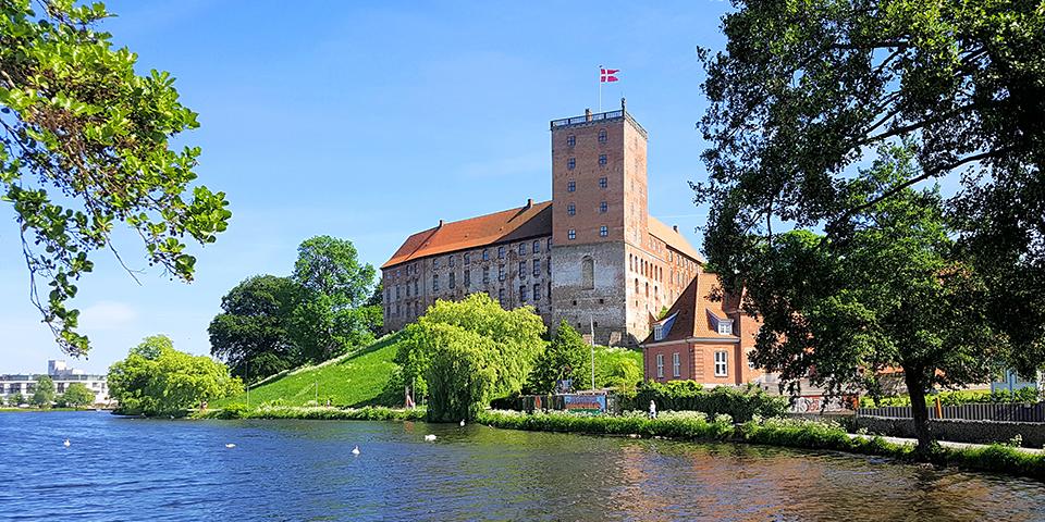 Koldinghus ligger flot ved slotssøen i Kolding.