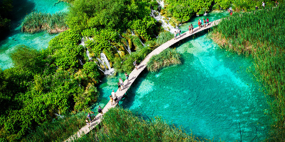 Gangbro over turkisblåt vand i Plitvice nationalpark.