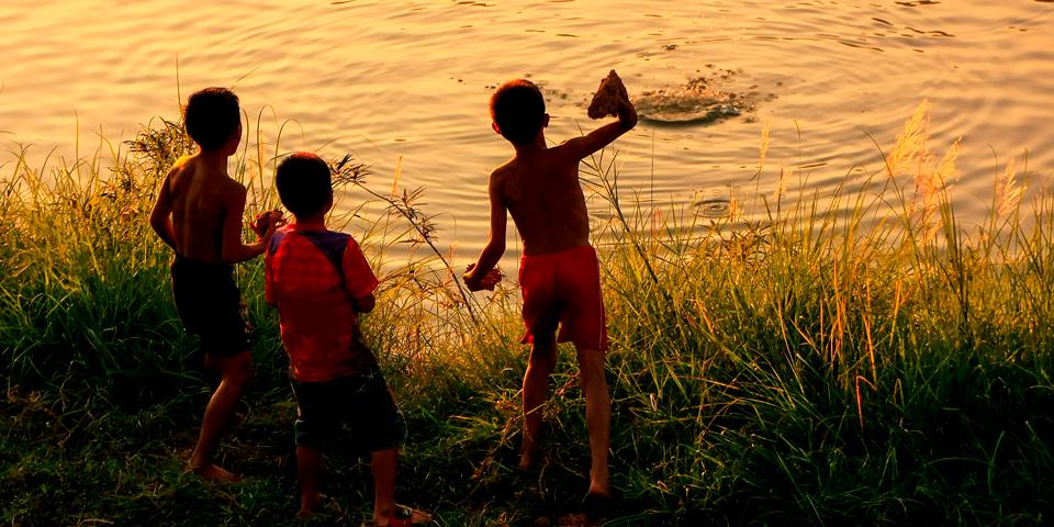 Lokale børn leger ved Mekongfloden i Vientiane.