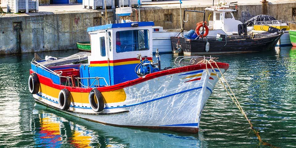 I havnen ligger de farverige fiskerbåde som kaldes Aiolas.
