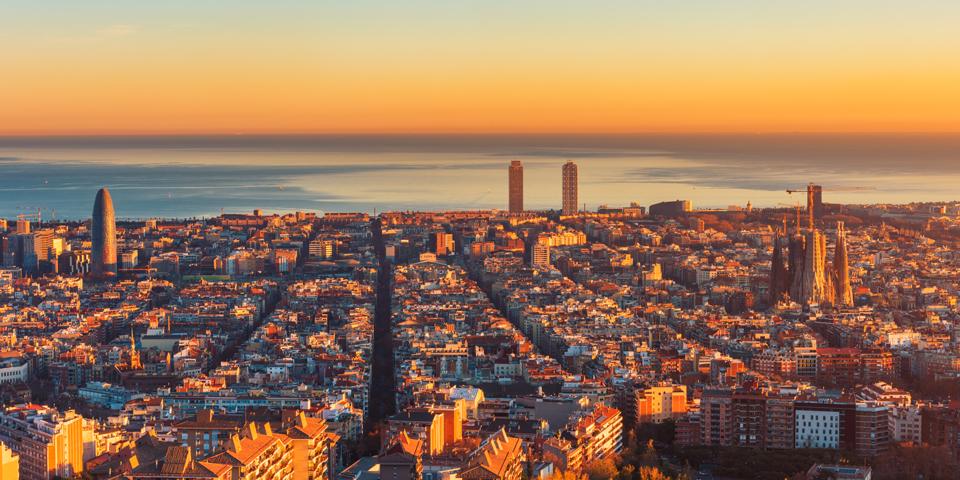 Solen går ned bag Gaudís Barcelona.