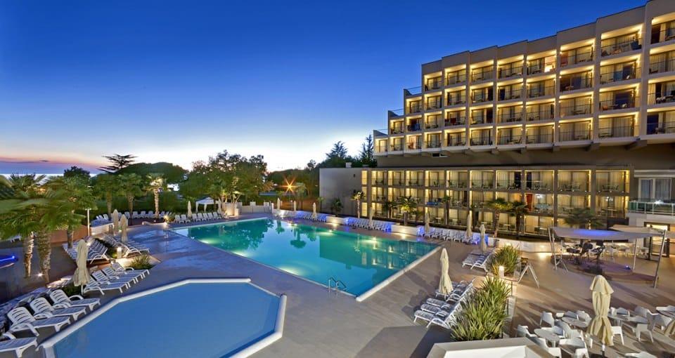 Hotellets lækre poolområde smukt oplyst ved aftentiden.