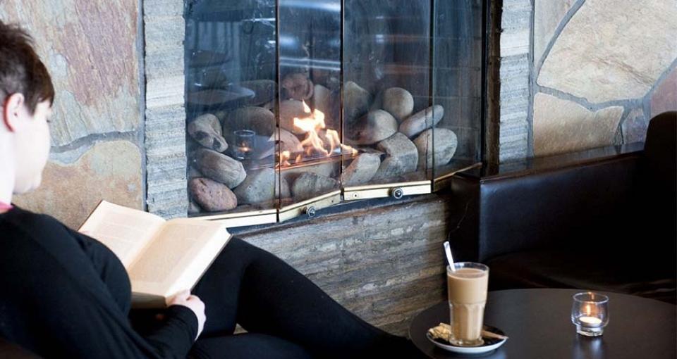 Afslapning og kaffe ved pejsen på Radisson Blu Polar Hotel Spitsbergen.
