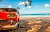 Gammel amerikanerbil på stranden på Cuba.