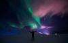 Mand foran nordlys på Svalbard.