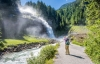 Turist tager billeder af Krimmlervandfaldene.