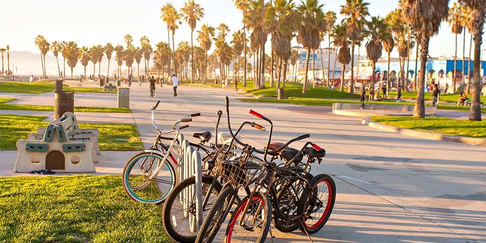 Solnedgang på den verdensberømte strandpromenade i Venice Beach.
